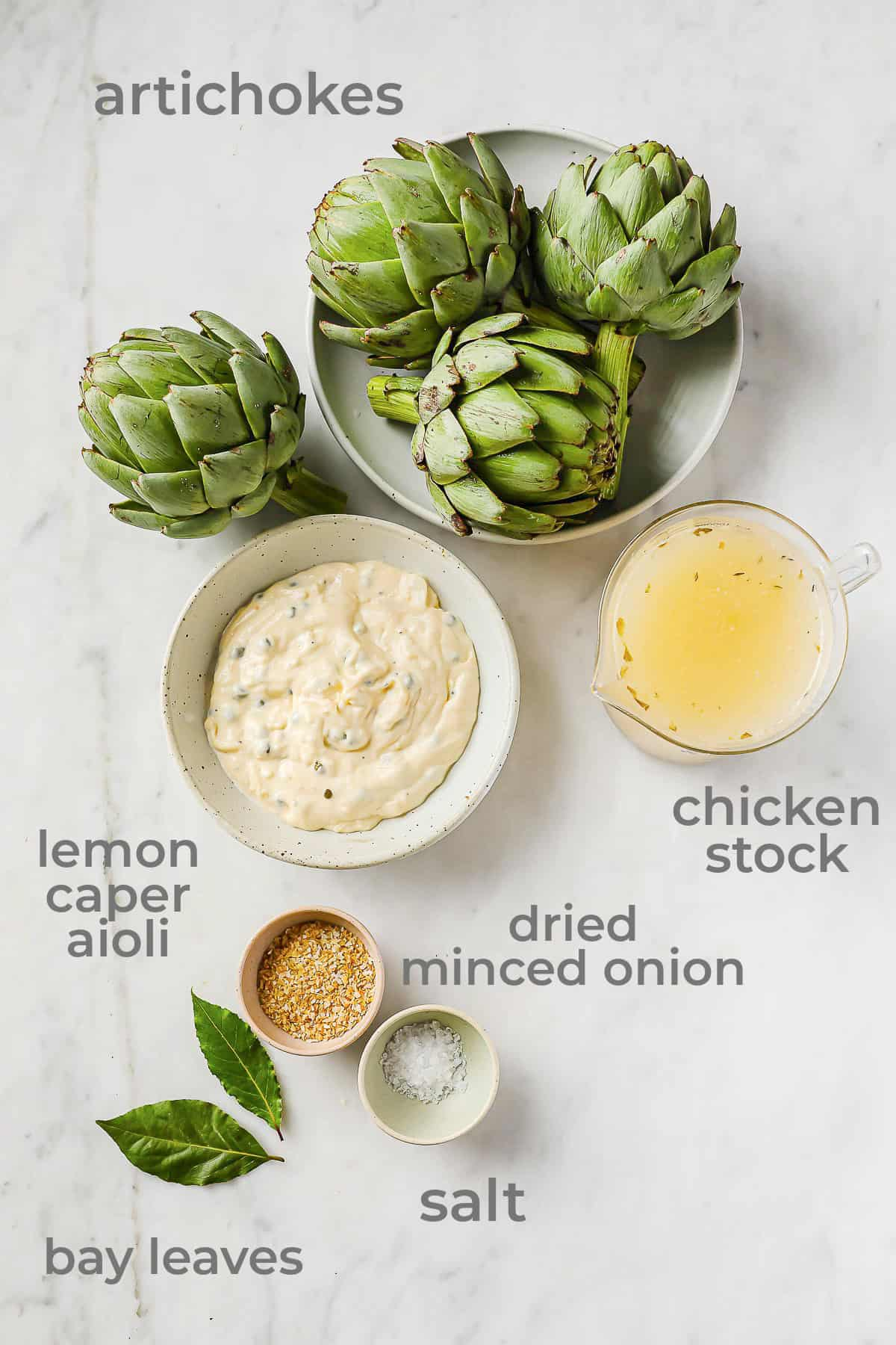 artichokes, aioli, chicken stock, dried minced onion, salt, and bay leaves all laid out in individual bowls, on a marble background